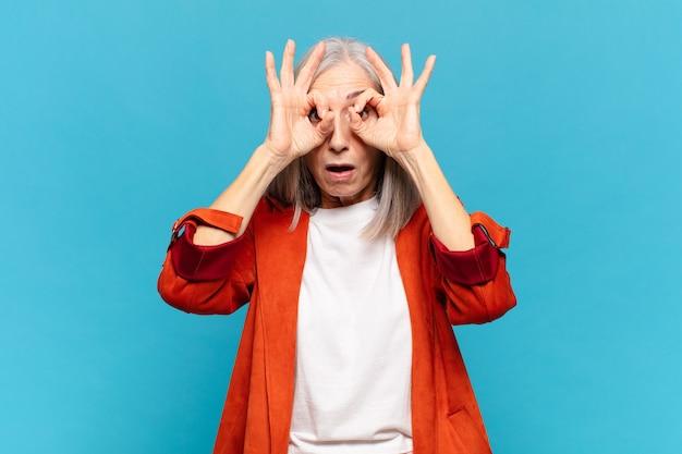 Vrouw van middelbare leeftijd die zich geschokt, verbaasd en verrast voelt, een bril vasthoudt met een verbaasde, ongelovige blik