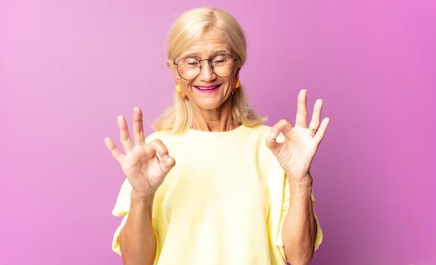 Vrouw van middelbare leeftijd die zich geschokt, verbaasd en verrast voelt, goedkeuring toont en met beide handen een goed teken maakt