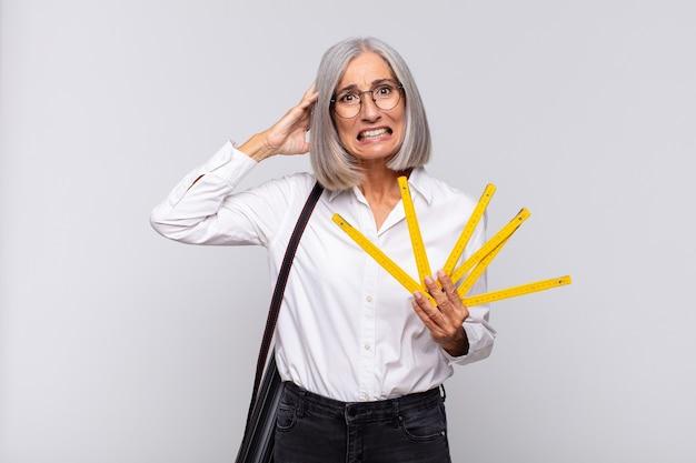 Vrouw van middelbare leeftijd die zich gestrest, bezorgd, angstig of bang voelt, met de handen op het hoofd, in paniek raakt bij een vergissing. architect concept