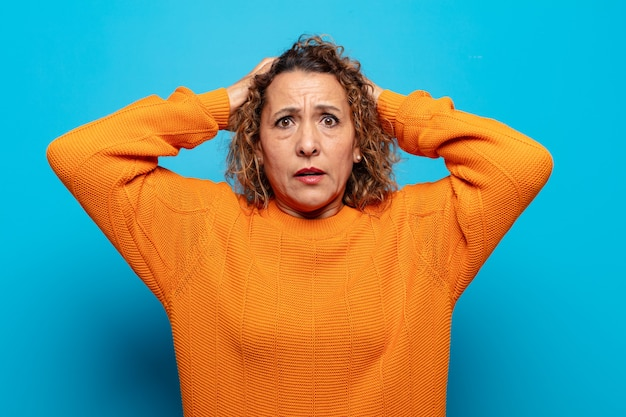 Vrouw van middelbare leeftijd die zich gestrest, bezorgd, angstig of bang voelt, met de handen op het hoofd, in paniek raakt bij een vergissing