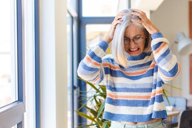 Vrouw van middelbare leeftijd die zich gestrest en gefrustreerd voelt, haar handen naar het hoofd steekt, zich moe, ongelukkig en met migraine voelt