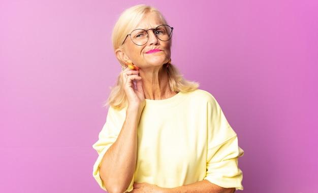 Vrouw van middelbare leeftijd die zich gestrest, gefrustreerd en moe voelt, pijnlijke nek wrijft, met een bezorgde, onrustige blik