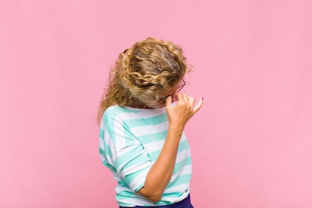 Vrouw van middelbare leeftijd die zich gestrest, ongelukkig en gefrustreerd voelt, het voorhoofd aanraakt en lijdt aan migraine of ernstige hoofdpijn