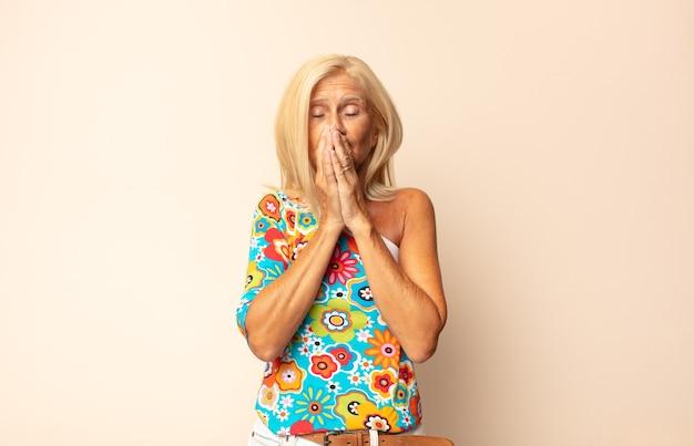 Vrouw van middelbare leeftijd die zich ongerust, boos en bang voelt, de mond bedekt met handen, er angstig uitziet en het verprutst