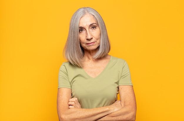 Vrouw van middelbare leeftijd die zich ontevreden en teleurgesteld voelt, er serieus, geïrriteerd en boos uitziet met gekruiste armen
