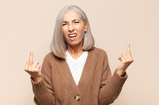Vrouw van middelbare leeftijd die zich provocerend, agressief en obsceen voelt, de middelvinger omdraait, met een rebelse houding