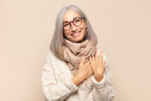 Vrouw van middelbare leeftijd die zich romantisch, gelukkig en verliefd voelt, vrolijk lacht en hand in hand dicht bij het hart houdt
