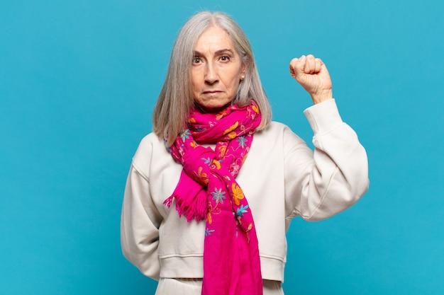 Vrouw van middelbare leeftijd die zich serieus, sterk en rebels voelt, haar vuist opstak, protesteert of vecht voor revolutie