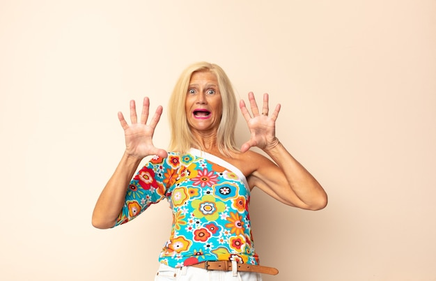 Vrouw van middelbare leeftijd die zich stomverbaasd en bang voelt, bang is voor iets beangstigend, met de handen naar voren en zegt: blijf weg