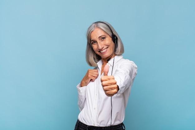 Vrouw van middelbare leeftijd die zich trots, zorgeloos, zelfverzekerd en gelukkig voelt, positief glimlachend met omhoog duimen. telemarketeer concept