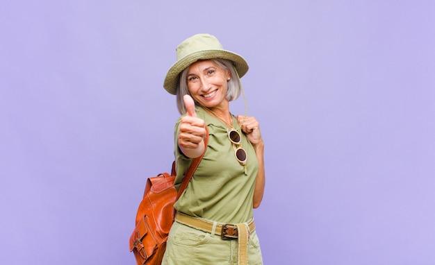 Vrouw van middelbare leeftijd die zich trots, zorgeloos, zelfverzekerd en gelukkig voelt, positief glimlachend met omhoog duimen
