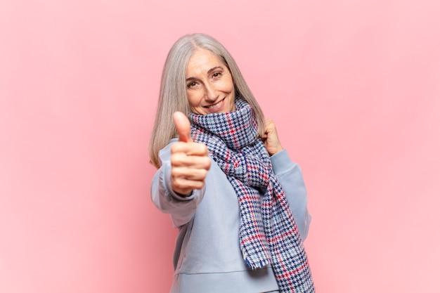 Vrouw van middelbare leeftijd die zich trots, zorgeloos, zelfverzekerd en gelukkig voelt, positief glimlacht met omhoog duimen