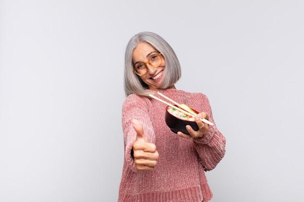 Vrouw van middelbare leeftijd die zich trots, zorgeloos, zelfverzekerd en gelukkig voelt, positief glimlacht met thumbs up aziatisch eten concept