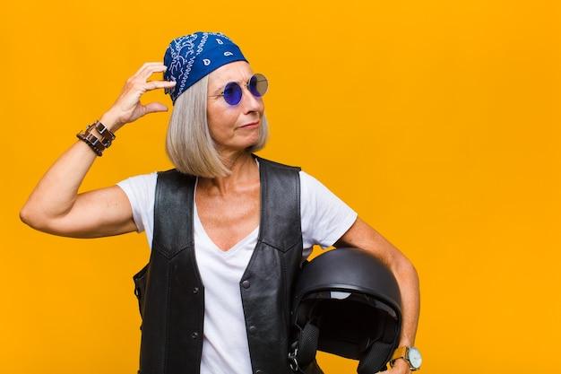 Vrouw van middelbare leeftijd die zich verbaasd en verward voelt, haar hoofd krabt en naar de zijkant kijkt