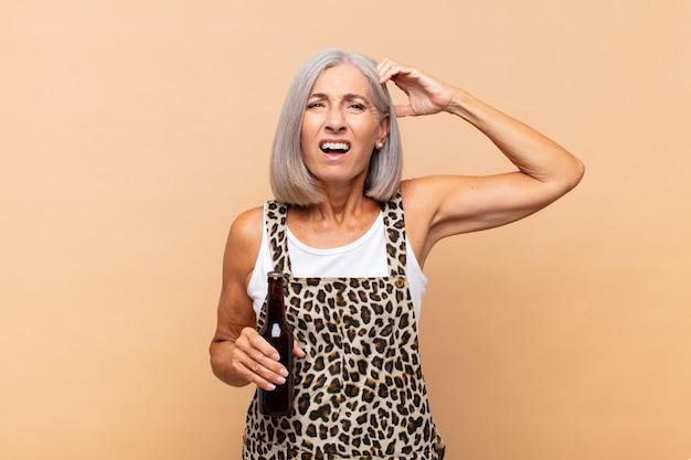 Vrouw van middelbare leeftijd die zich verbaasd en verward voelt, haar hoofd krabt en opzij kijkt met een biertje