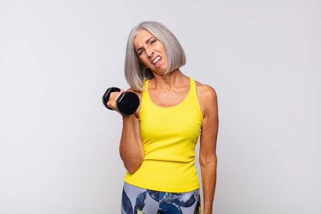 Vrouw van middelbare leeftijd die zich verbaasd en verward voelt, met een domme, verbijsterde uitdrukking op zoek naar iets onverwachts. fitness concept