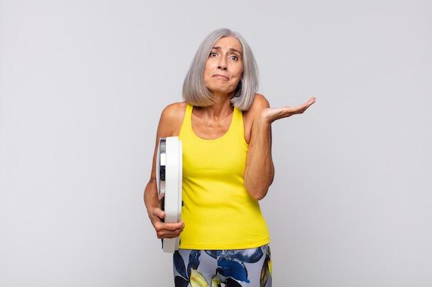 Vrouw van middelbare leeftijd die zich verbaasd en verward voelt, twijfelt, weegt of verschillende opties kiest met een grappige uitdrukking. fitness concept