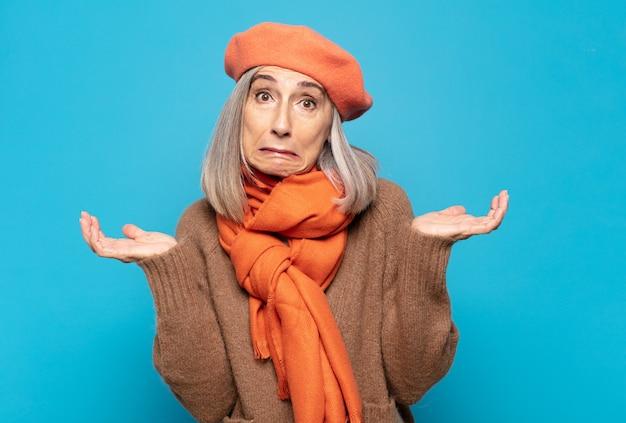 Vrouw van middelbare leeftijd die zich verbaasd en verward voelt, twijfelt, weegt of verschillende opties kiest met een grappige uitdrukking