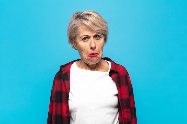 Vrouw van middelbare leeftijd die zich verdrietig en gestrest voelt, van streek is vanwege een onaangename verrassing, met een negatieve, angstige blik