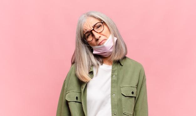 Vrouw van middelbare leeftijd die zich verdrietig en zeurderig voelt met een ongelukkige blik, huilt met een negatieve en gefrustreerde houding