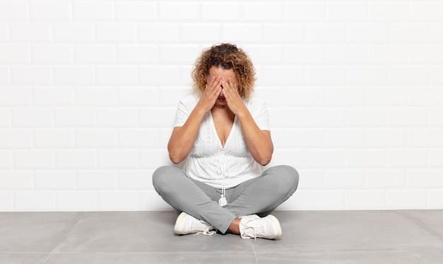 Vrouw van middelbare leeftijd die zich verdrietig, gefrustreerd, nerveus en depressief voelt, haar gezicht met beide handen bedekt, huilt
