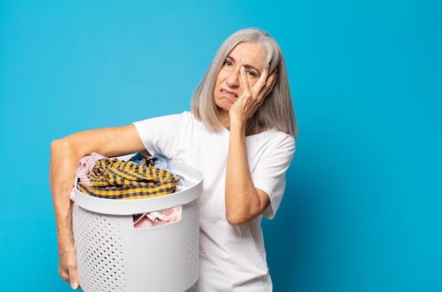Vrouw van middelbare leeftijd die zich verveeld, gefrustreerd en slaperig voelt na een vermoeiende, saaie en vervelende taak, gezicht met hand vasthoudend