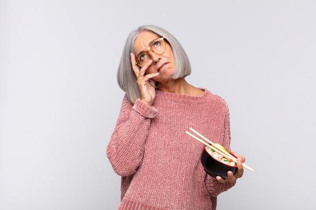 Vrouw van middelbare leeftijd die zich verveeld, gefrustreerd en slaperig voelt na een vermoeiende, saaie en vervelende taak, gezicht vasthoudend met hand aziatisch eten concept