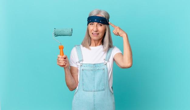 Vrouw van middelbare leeftijd die zich verward en verbaasd voelt en laat zien dat je gek bent met een roller die een muur schildert