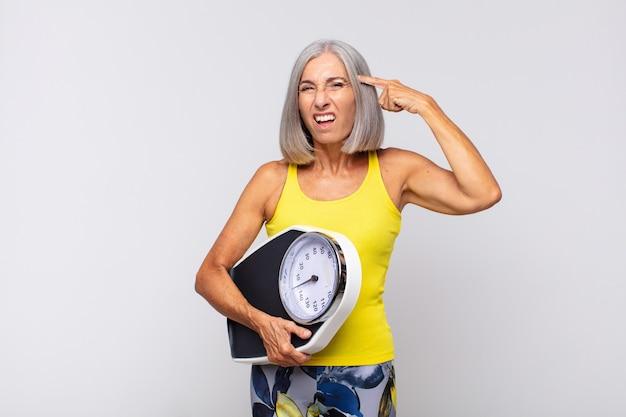 Vrouw van middelbare leeftijd die zich verward en verbaasd voelt en laat zien dat je gek, gek of gek bent. fitnessconcept