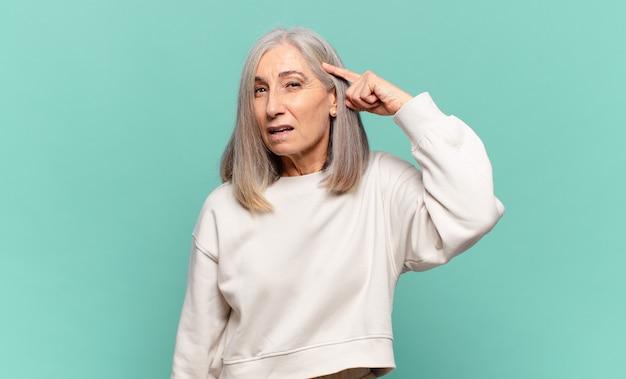 Vrouw van middelbare leeftijd die zich verward en verbaasd voelt en laat zien dat je gek, gek of gek bent