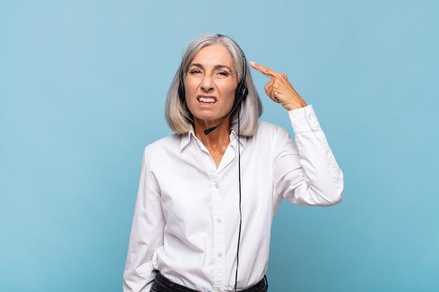 Vrouw van middelbare leeftijd die zich verward en verbaasd voelt, laat zien dat je gek bent
