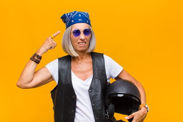 Vrouw van middelbare leeftijd die zich verward en verbaasd voelt, laat zien dat je gek, gek of gek bent