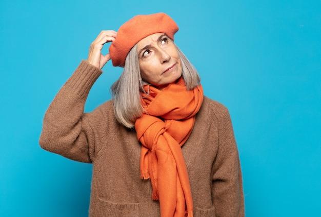 Vrouw van middelbare leeftijd die zich verward en verward voelt, haar hoofd krabt en opzij kijkt