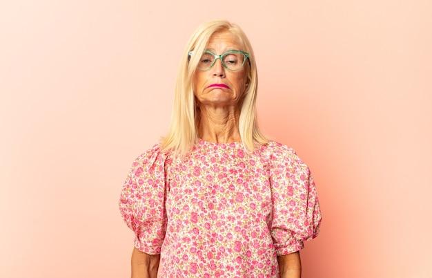 Vrouw van middelbare leeftijd die zich verward of vol voelt of twijfels en vragen geïsoleerd