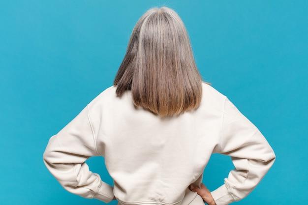Vrouw van middelbare leeftijd die zich verward of vol voelt of twijfels en vragen, zich afvragend, met de handen op de heupen, achteraanzicht