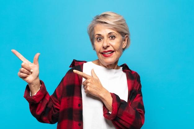 Vrouw van middelbare leeftijd die zich vrolijk en verrast voelt, met een geschokte uitdrukking glimlacht en naar de zijkant wijst
