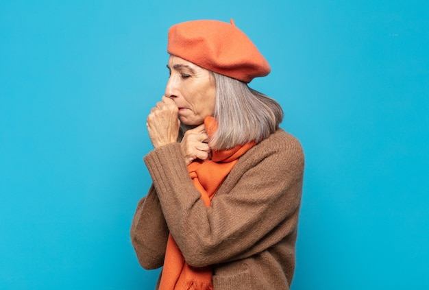 Vrouw van middelbare leeftijd die zich ziek voelt met keelpijn en griepsymptomen, hoesten met bedekte mond
