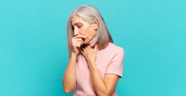 Vrouw van middelbare leeftijd die zich ziek voelt met keelpijn en griepsymptomen