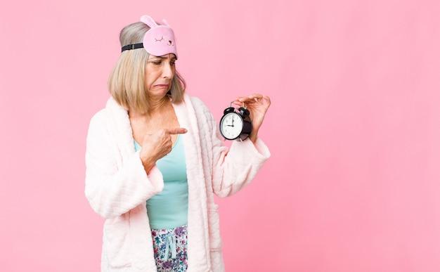 Vrouw van middelbare leeftijd dragen nacht pak met een wekker