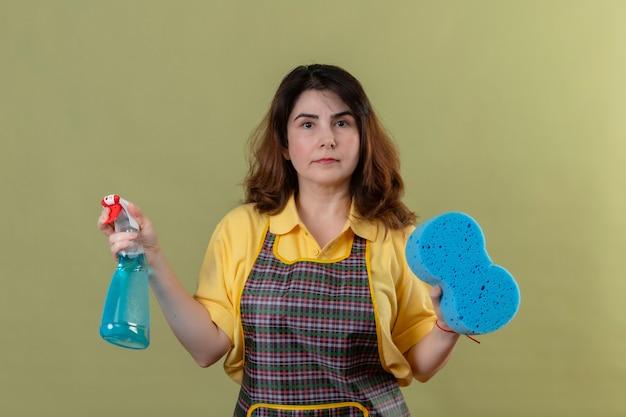 Vrouw van middelbare leeftijd dragen schort met schoonmaak spray en spons met zelfverzekerde ernstige uitdrukking op gezicht staande over groene muur