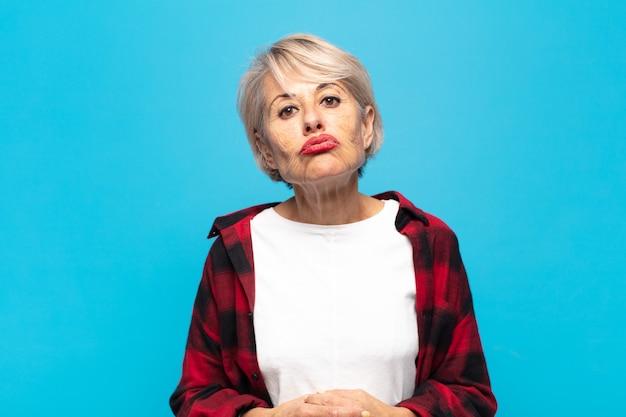 Vrouw van middelbare leeftijd drukt lippen samen met een schattige, leuke, vrolijke, mooie uitdrukking, die een kus verzendt