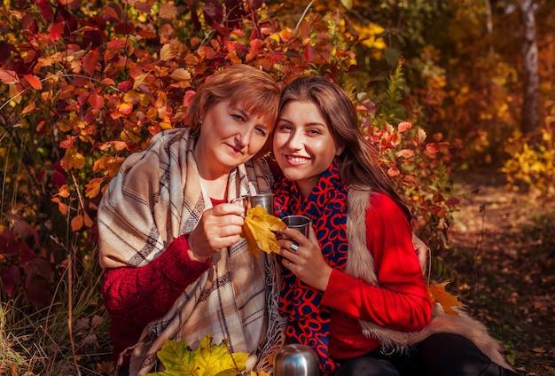 Vrouw van middelbare leeftijd en haar dochter die thee drinken in het herfstbos