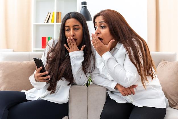 Vrouw van middelbare leeftijd en haar jonge dochter in witte overhemden en zwarte broek zittend op de stoelen dochter en haar moeder met smartphone kijken verbaasd en verrast in lichte woonkamer