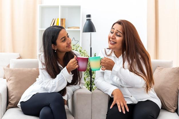 Vrouw van middelbare leeftijd en haar jonge dochter in witte overhemden en zwarte broek zittend op de stoelen met kopjes hete thee gelukkig en positief tijd samen doorbrengen in lichte woonkamer