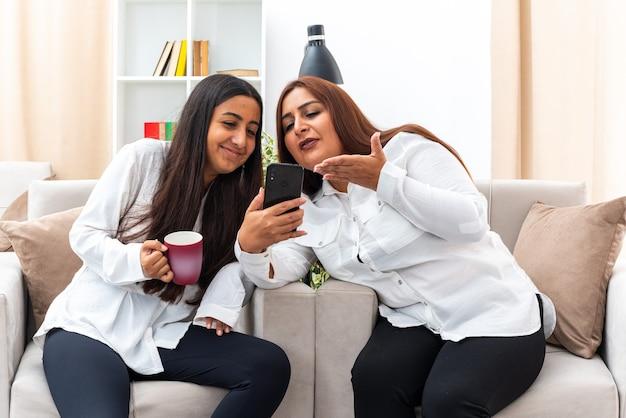 Vrouw van middelbare leeftijd en haar jonge dochter in witte overhemden en zwarte broek zittend op de stoelen met smartphone gelukkig en vrolijk tijd samen doorbrengen in lichte woonkamer