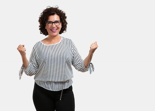 Vrouw van middelbare leeftijd erg blij en opgewonden, het verhogen van de armen