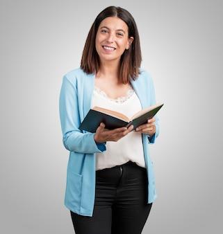 Vrouw van middelbare leeftijd geconcentreerd en lachend, met een leerboek, studerend om een examen te halen of een interessant boek te lezen
