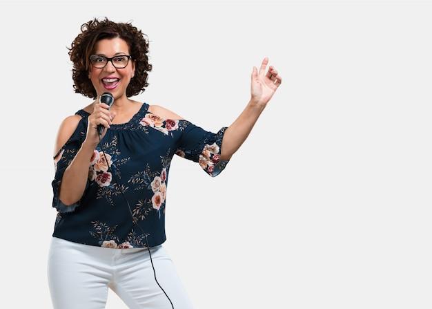 Vrouw van middelbare leeftijd, gelukkig en gemotiveerd, een lied zingen met een microfoon, een evenement presenteren of een feestje vieren, geniet van het moment
