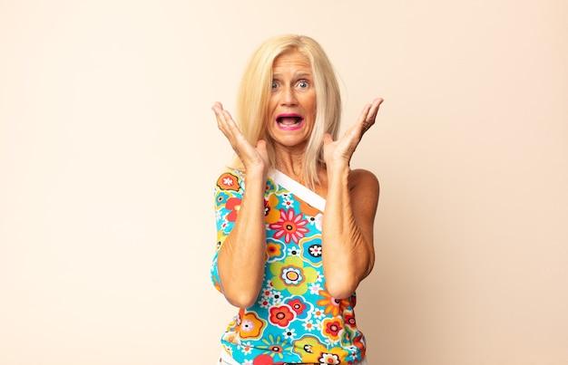 Vrouw van middelbare leeftijd geschokt en opgewonden voelen, geïsoleerd lachen