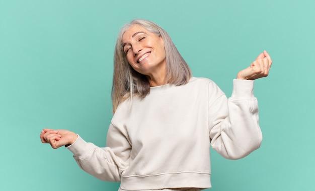 Vrouw van middelbare leeftijd glimlachen, zich onbezorgd, ontspannen en gelukkig voelen, dansen en naar muziek luisteren, plezier maken op een feestje